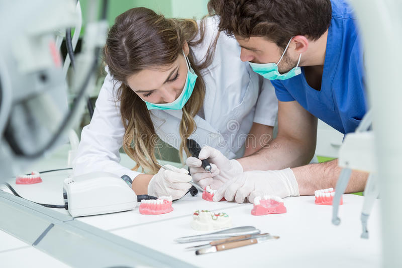 Prothèse dentaire, dentiers, travail de prosthétique Mains de prosthétique tout en travaillant au dentier, aux dents fausses, à u image stock