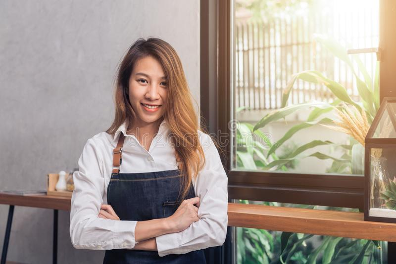 Protrait av den unga asiatiska kvinnliga baristavälkomnandet hennes kund till coffee shop i varm ljus eftermiddag med ett härligt arkivbild
