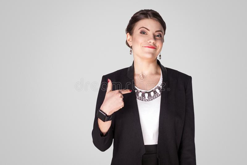 Proud, airy businesswoman pointing finger himself and toothy smile. Studio shot, indoor. Isolated on grey background royalty free stock images
