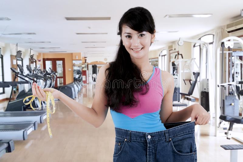 Proud asian woman showing her weight loss royalty free stock photo
