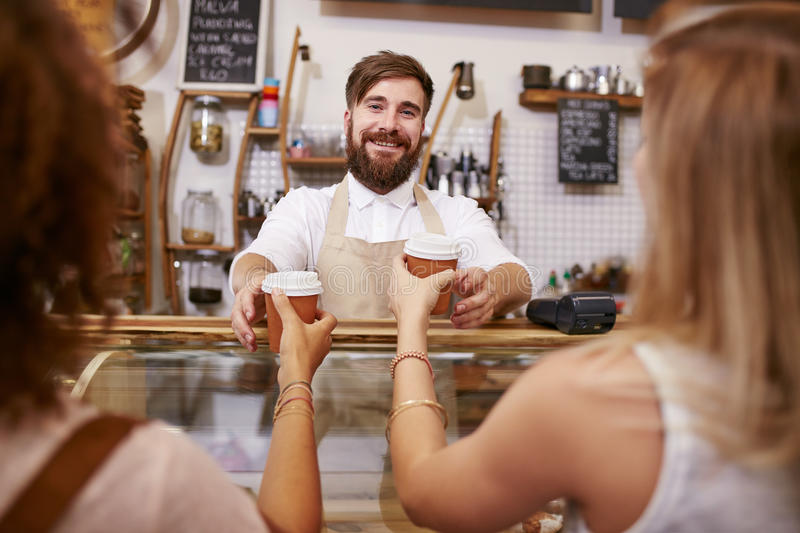 Proud barista standing in a coffee shop royalty free stock image