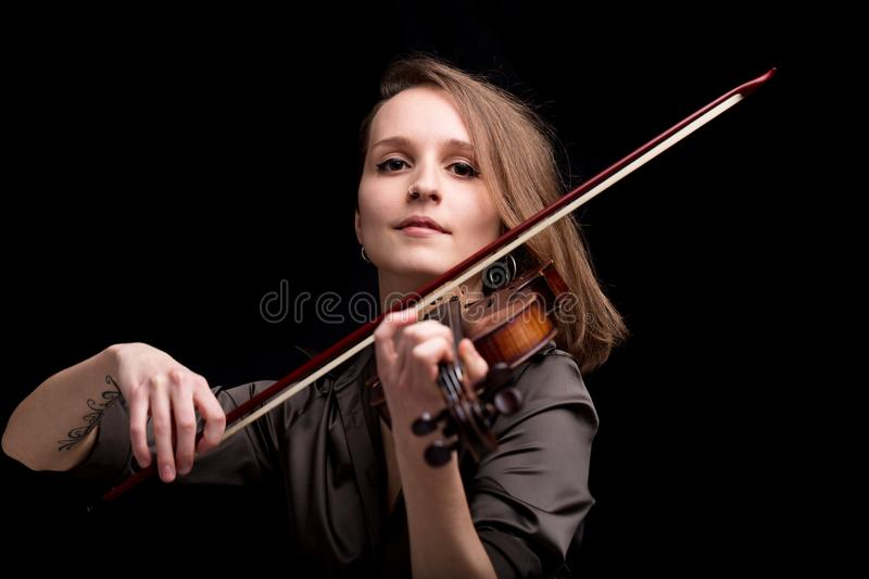Proud baroque violinist playing folk music. Young and proud woman playing a baroque violin on a black background royalty free stock photo