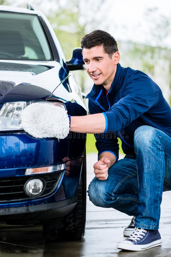 Proud car owner cleaning the headlamps. Of his luxury sedan with a soft absorbent mitt royalty free stock photos