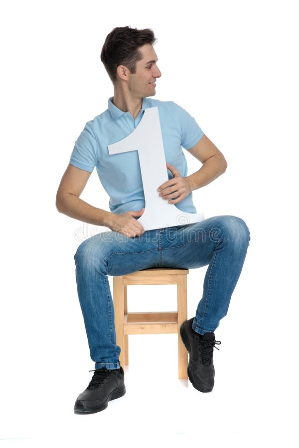 Proud casual guy holding a number one. And looking to the side while wearing a blue polo shirt and sitting on a chair on white studio background royalty free stock photos