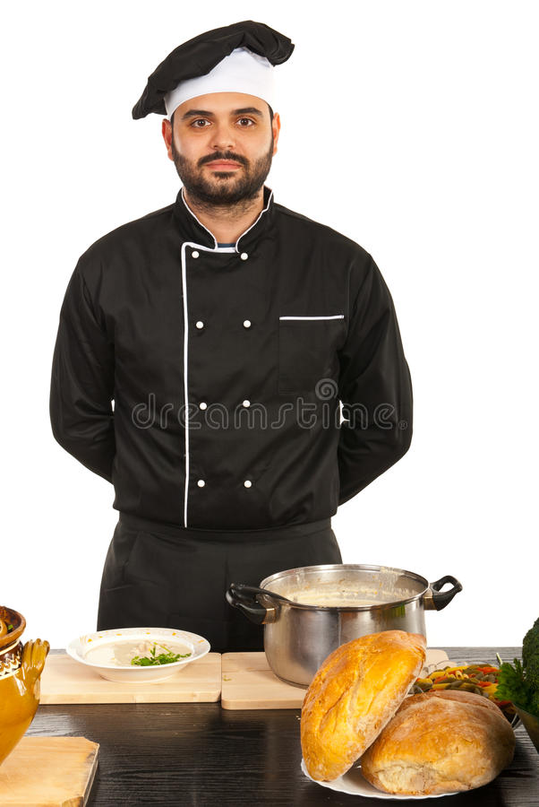 Proud chef male. Standing in kitchen with food on table stock images