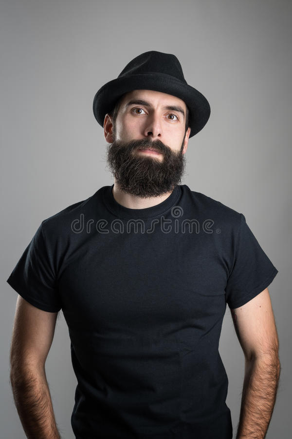 Proud confident bearded hipster wearing black t-shirt and hat looking at camera. Headshot portrait over gray studio background with vignette stock images