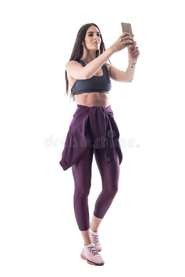 Proud confident fitness young woman taking selfie with mobile phone after gym exercises. royalty free stock images