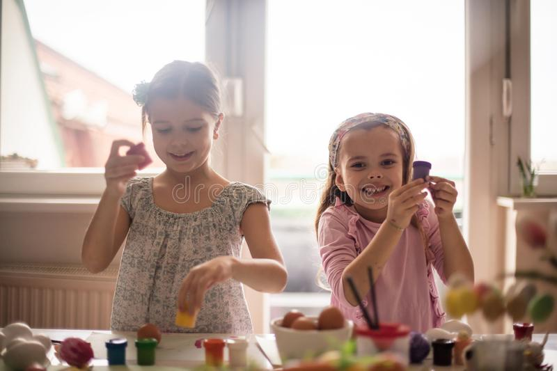 Proud of Easter creativity. Little girls coloring Easter egg stock photography