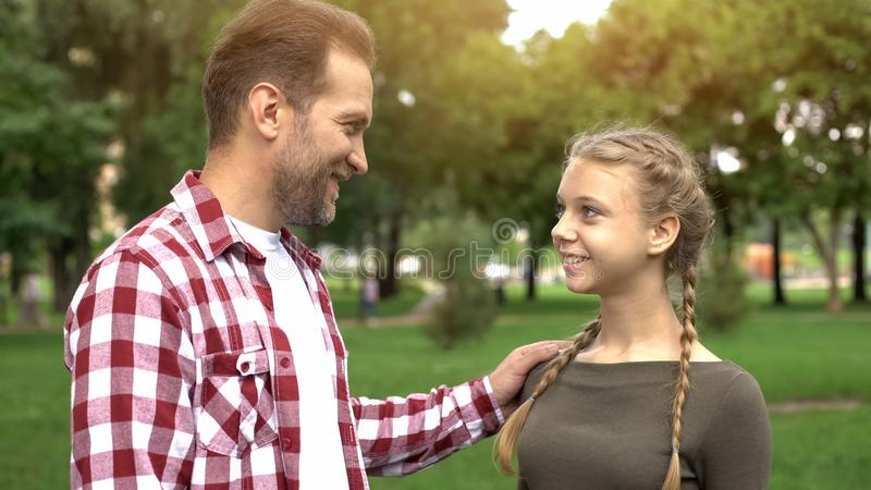 Proud father looking at daughter, congratulating with university entry, success. Stock photo stock photography