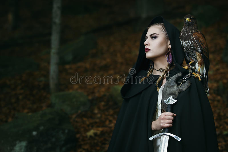 Proud female warrior with hawk. Dark woods background stock images