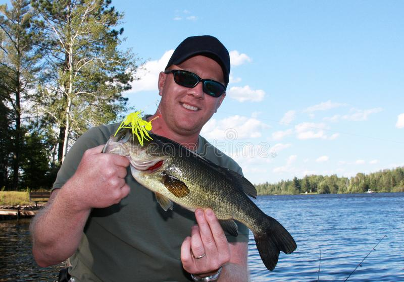 Proud fisherman with a Large Mouth Bass. Proud fisherman in a boat with a Large Mouth Bass with a blue summer sky in the background stock photography