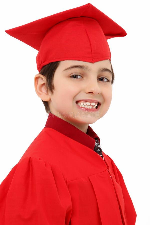 Proud Kindergarten Graduate Child. Attractive young kindergarten graduate in red cap and gown over white stock photos
