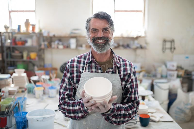 Proud male potter showing his creation to camera. In the pottery workshop stock photos