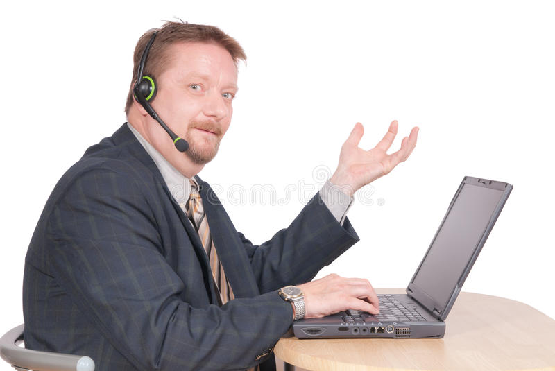 Proud manager in conference call. Proud middle-aged dominant manager or business leader in a conference call with headset sitting at his laptop PC, making a royalty free stock image