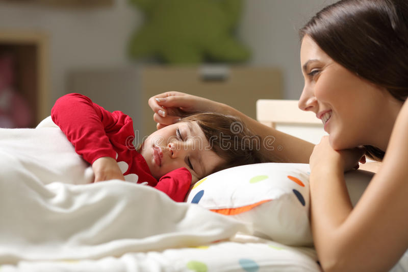 Proud mother watching to sleep to her daughter stock photography