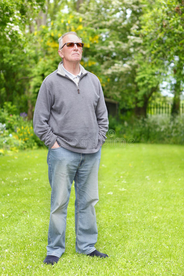 Proud old man on lawn. Proud old senior man standing on his lawn and is looking up and thinking stock photography