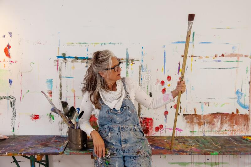Proud older artist woman, in her fifties with grey hair and black glasses holds a big paintbrush. Proud older artist woman, in her fifties with grey hair and royalty free stock image