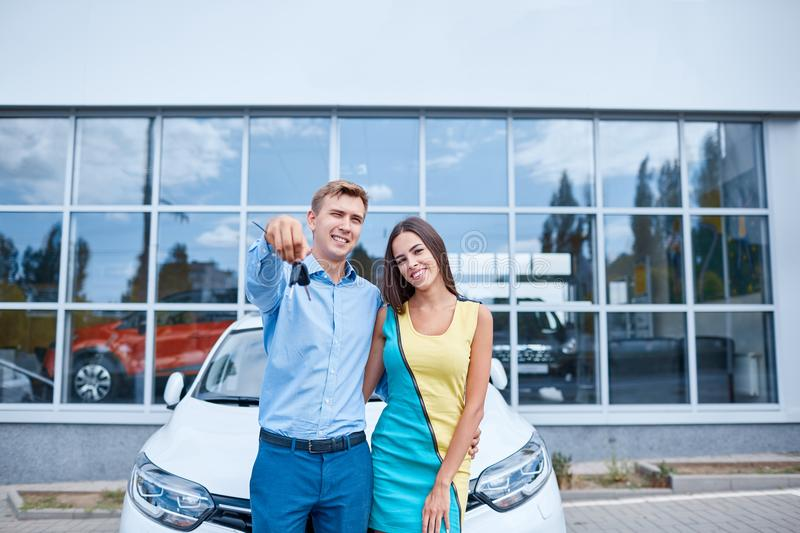 The family bought a new car in the showroom. The concept of buying a new car. stock photography