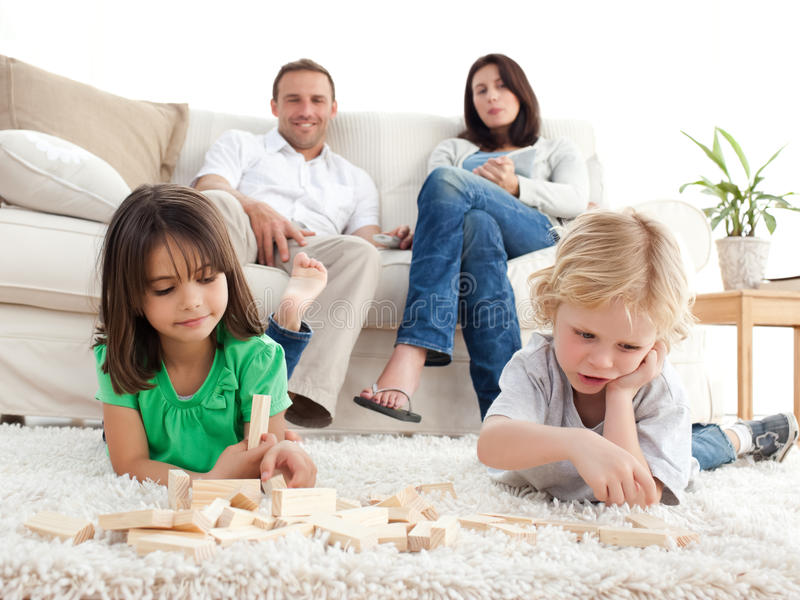 Download Proud Parents Looking At Their Children Playing Stock Photo - Image of glad, assemble: 17469620