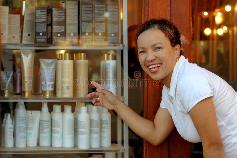 Proud shop owner. A young colored multiracial beautiful woman with proud expression in her pretty face at work showing the new products in her own hairdresser
