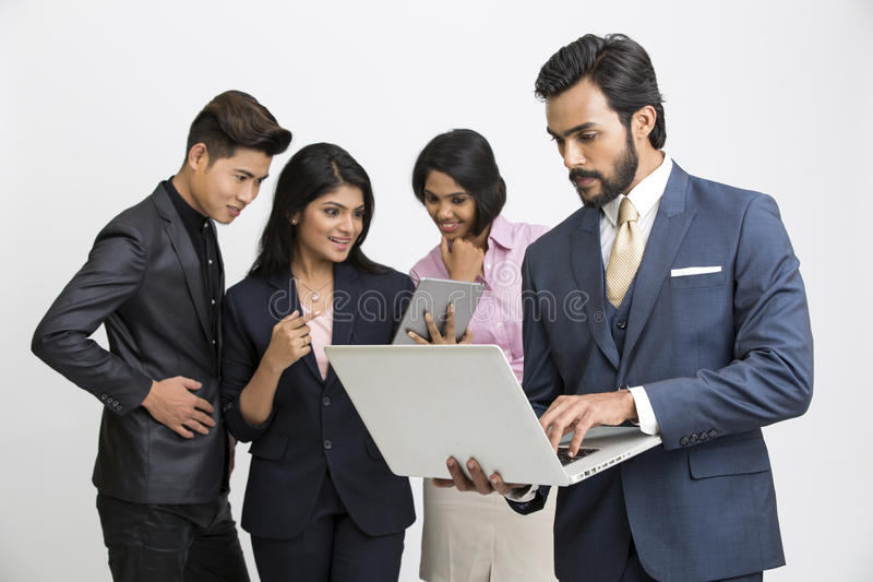 Proud smiling businessman working in laptop with his team business people stock photography