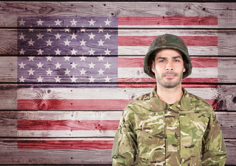 Proud soldier against wooden american flag background stock images
