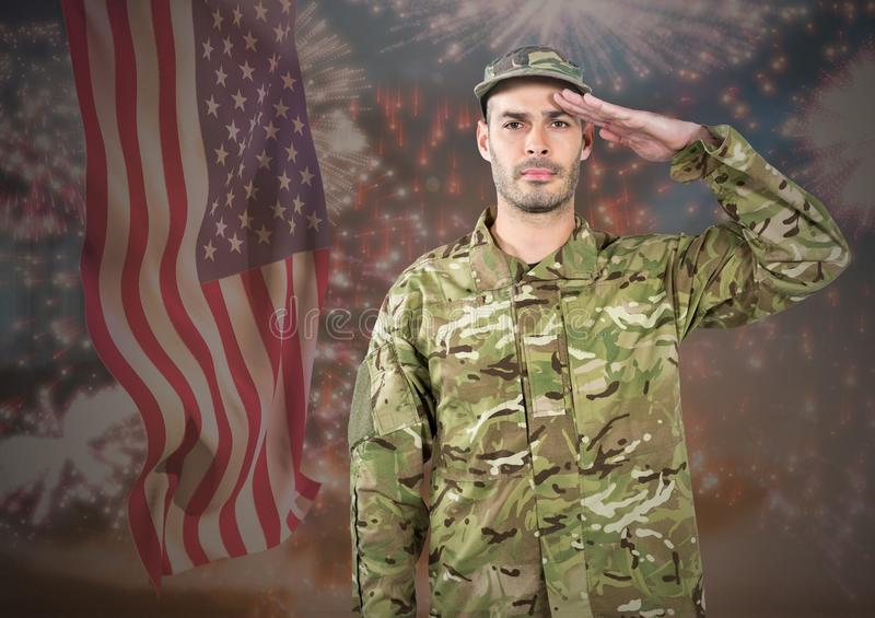 Proud soldier saluting against fluttering american flag and fireworks in background royalty free stock photos