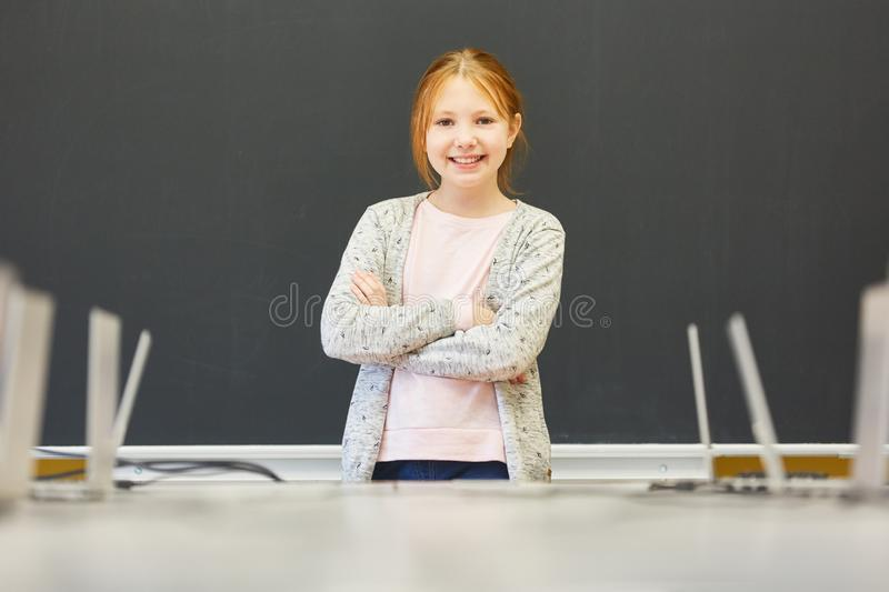 Proud student with crossed arms. Proud student stands with crossed arms in front of the blackboard in class royalty free stock images