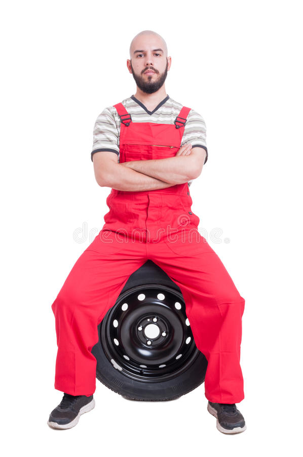 Proud and successful mechanic sitting on car wheel royalty free stock photos