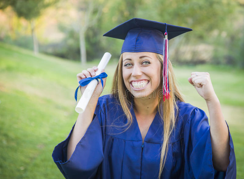 Proud Teen Graduate Holding Diploma in Cap and Gown stock photo