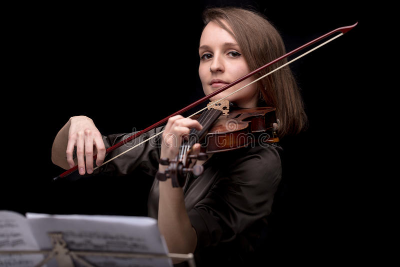 Proud violinist woman with her violin and bow. Young beautiful woman violinist player playing her instrument on her shoulder holding bow. portrait in a blurred stock photos