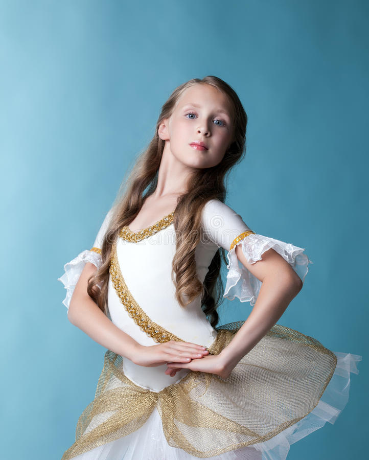 Proud young ballerina posing on blue backdrop stock image