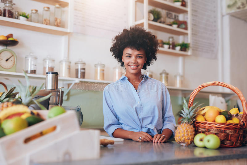 Proud young female juice bar owner. Portrait of beautiful young woman standing at counter in juice bar smiling to camera. African female juice bar owner stock photo