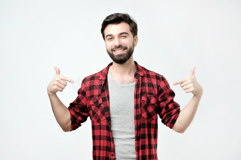 Proud young man, standing, pointing himself and looking at camera with serious egoist face stock image