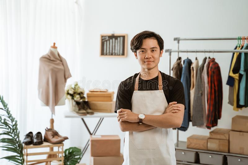 Proud young online ecommerce shop owner standing at his office. Smiling to camera royalty free stock photography