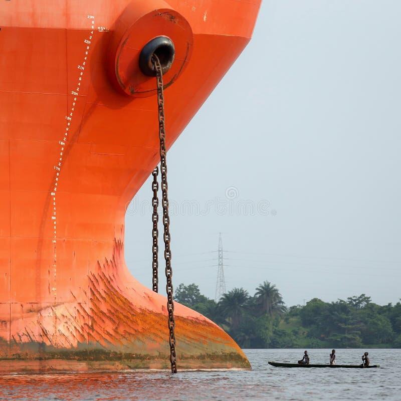 Proue d'un grand bateau face à face avec une petite pirogue en bois photo libre de droits
