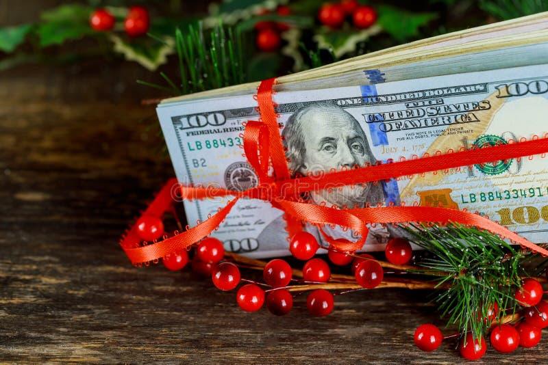 Proue rouge de bande de cadeau au-dessus des dollars américains Fond d'argent images stock