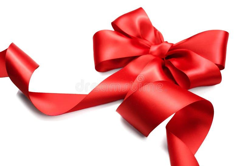 Proue rouge de cadeau de satin Ruban rouge d'isolement sur le blanc photographie stock