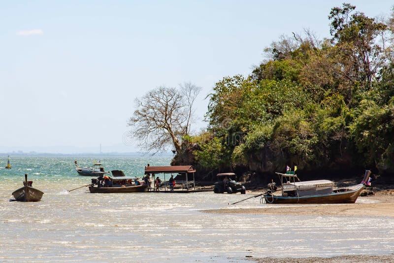 Província de Krabi, Tailândia - 12 de maio de 2019: Um trator pegara turistas de um barco na maré baixa Não há nenhuma outra mane fotografia de stock