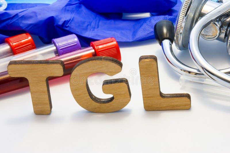 Prov för blod för triglyceride för TGL-abbreviaturemedel enkelt med labbrör med blod och stetoskopet Använda akronymen TGL i labo royaltyfri foto