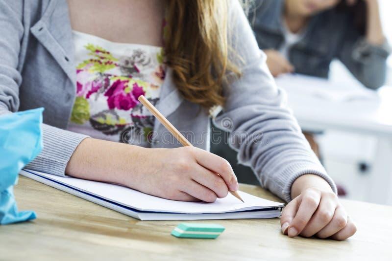 Prov för studentflickahandstil i klassrum royaltyfri fotografi