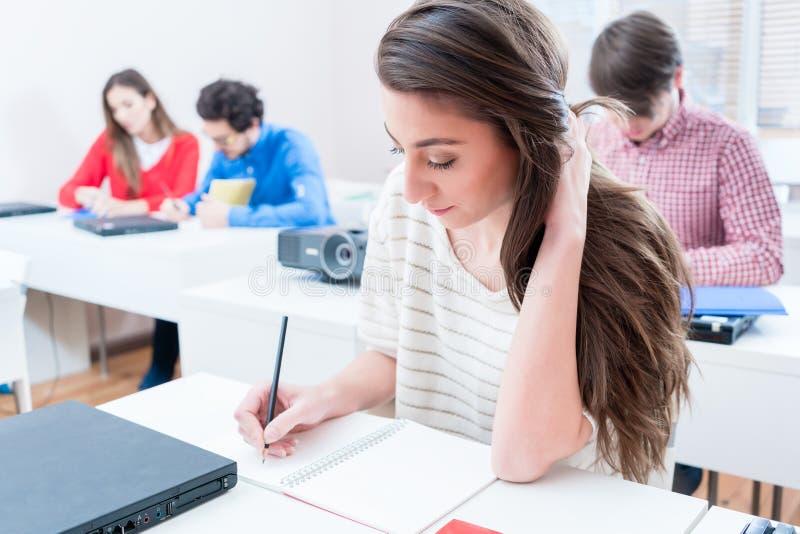 Prov för studentkvinnahandstil i seminariumrum av universitetet royaltyfria bilder