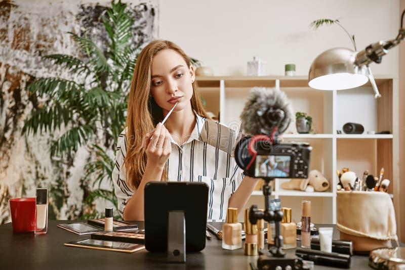 Prova del colore nuovo Giovane blogger femminile che prova un nuovo colore del rossetto mentre facendo nuova video esercitazione  fotografie stock libere da diritti