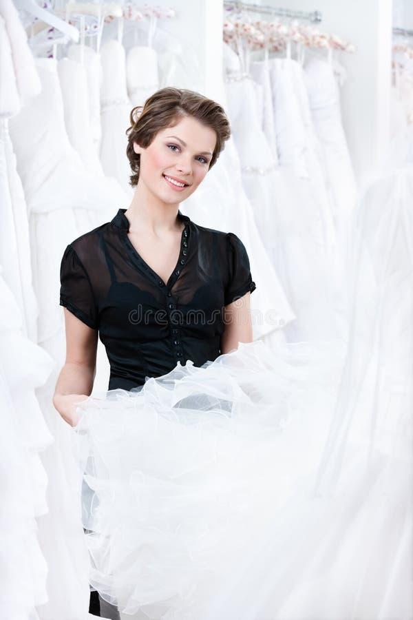 Prova Dell Assistente Di Negozio Per Selezionare Un Vestito Adeguato Fotografia Stock