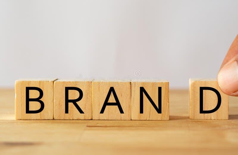 Prova dell'uomo della mano per completare la parola sul cubo di legno, concetto di marca di marca fotografie stock libere da diritti