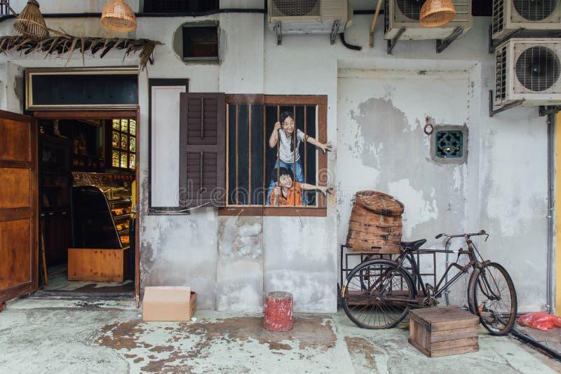 Prova dipinta dei bambini per rubare alimento dalla bici dell'alimento dal davanti del ristorante di George Town Penang, Malesia fotografia stock libera da diritti
