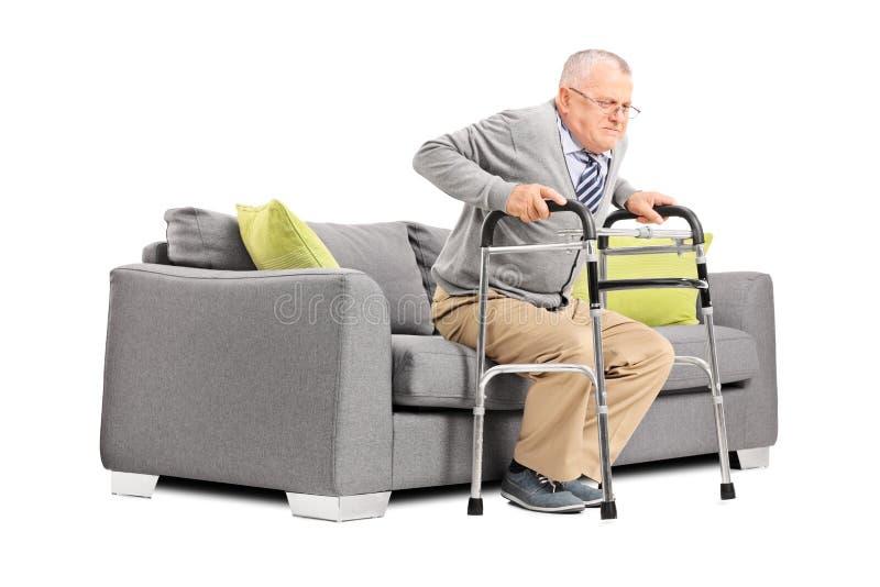 Prova senior di stare su con un camminatore immagine stock