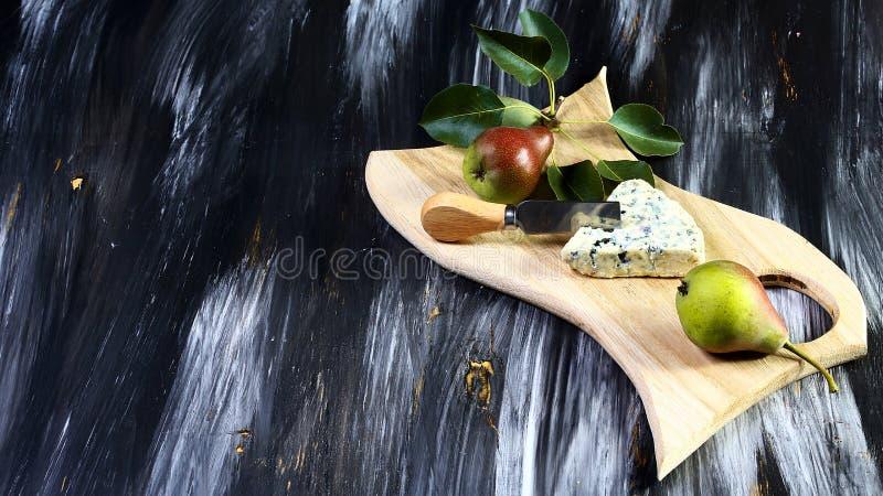 Provando o queijo do molde com peras dos frutos, e faca para o queijo no fundo de pedra do preto escuro Copie o espaço fotografia de stock royalty free