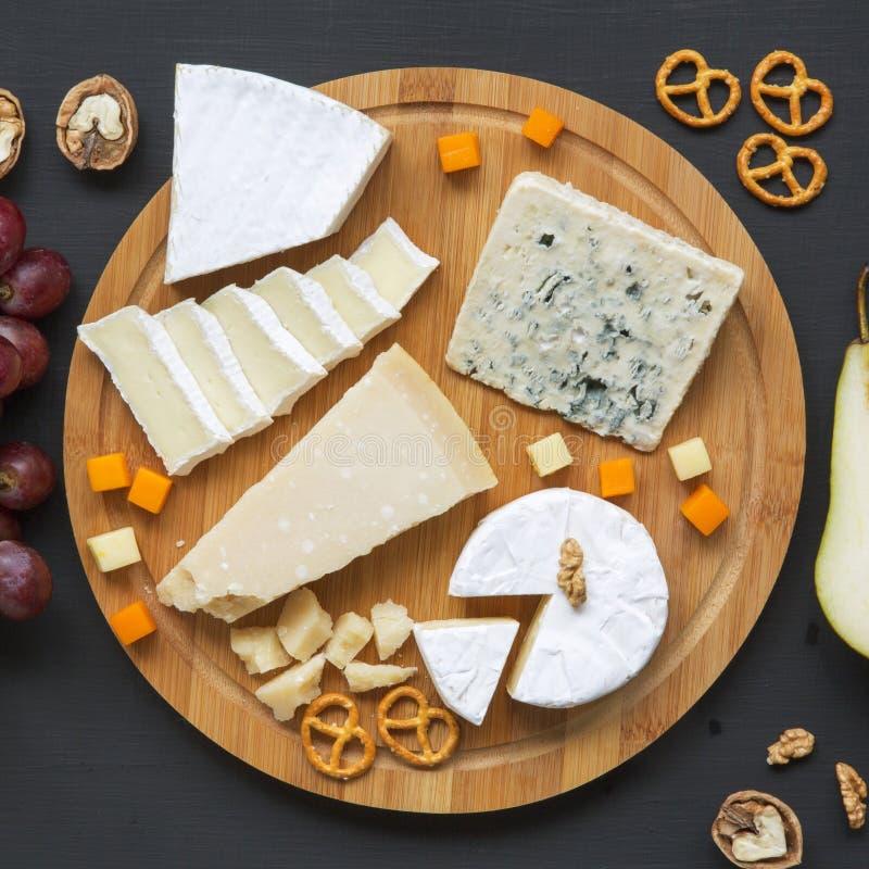 Provando o vário tipo de queijos na placa de madeira redonda com frutos, nozes e pretzeis Alimento para o vinho Vista superior, a imagens de stock