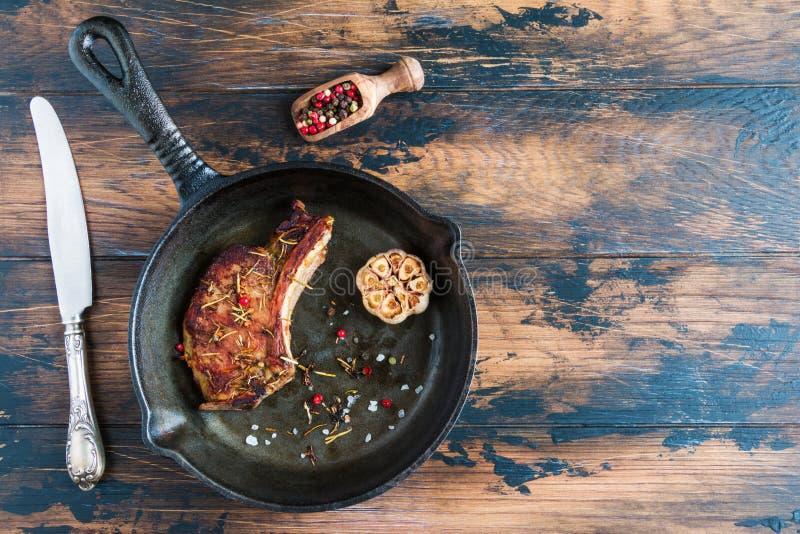Provea de costillas el filete del cerdo del ojo y el ajo cocido en sartén negra del arrabio en la tabla rústica de madera Pimient imagenes de archivo